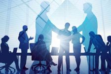 an abstract picture of business people round a meeting table with two businessmen shaking hands