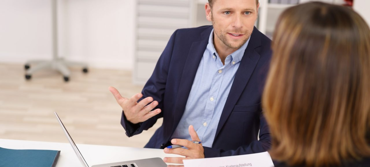 a picture of a businessman talking to a businesswoman at her desk